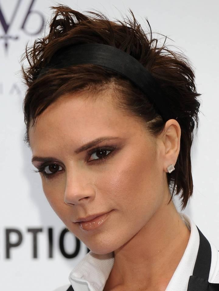 Victoria Beckham usa tiara de cetim preto com cabelo dividido lateralmente e bagunçadinho atrás.